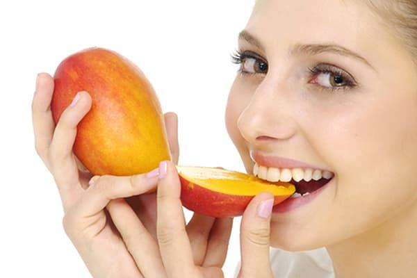 Fille mangeant de la mangue