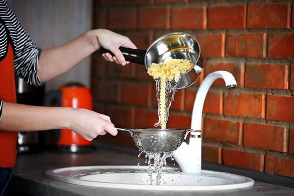 Femme draine l'eau après la cuisson des pâtes