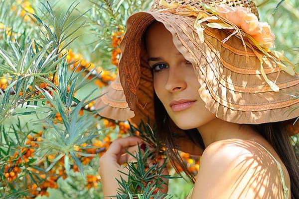 Fille au chapeau près d'un buisson d'argousier