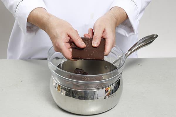 Un confiseur noie du chocolat dans un bain-marie