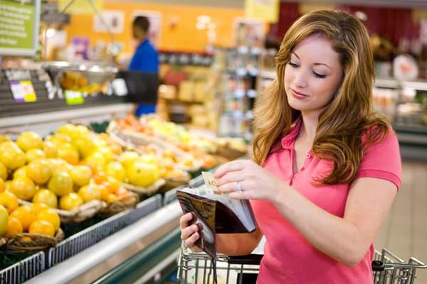 Vrouw in de winkel met een boodschappenlijstje