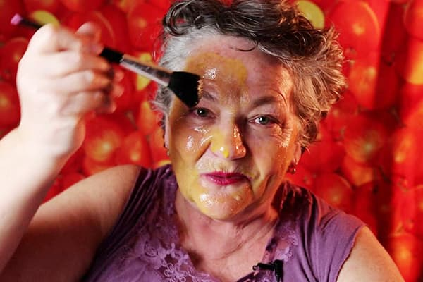 Une femme âgée met un masque d'oeuf sur son visage