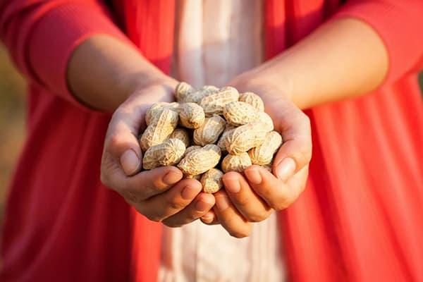 Femme avec une poignée de cacahuètes