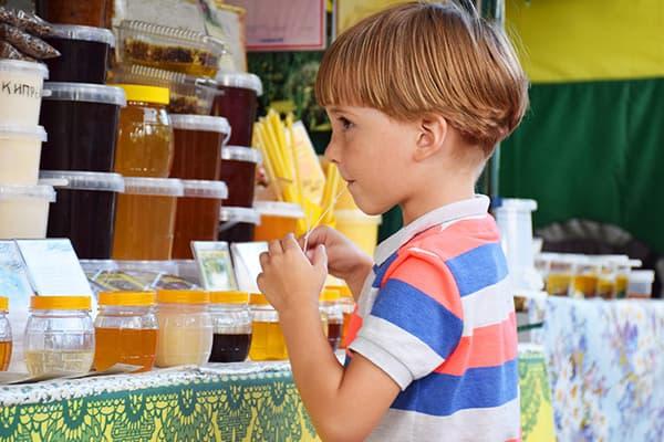 Un garçon goûte le miel à la foire