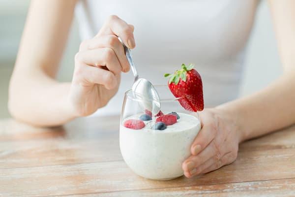 Fille mangeant du yaourt faible en gras avec des baies