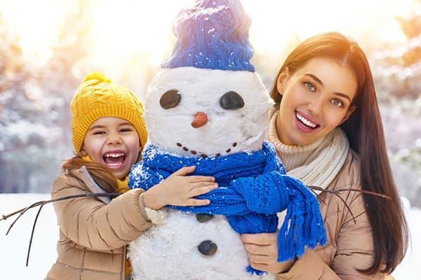 Maman et sa fille sculptent un bonhomme de neige